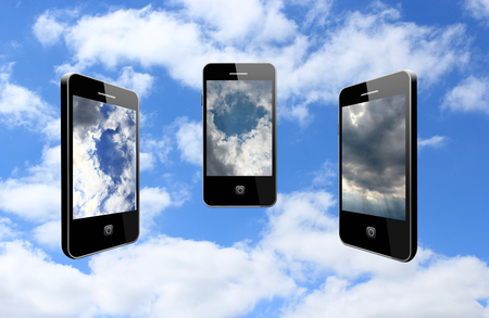 three modern mobile phones on the different cloudy sky photo