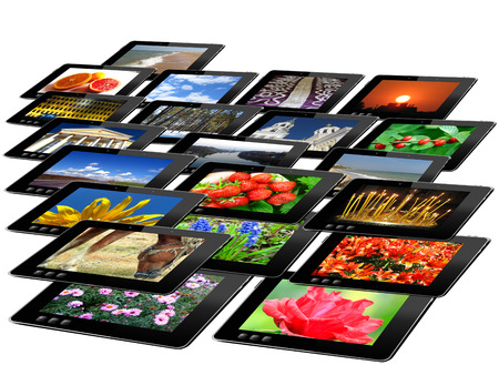 i pad: some black tablets with motley pictures isolated on white background Stock Photo
