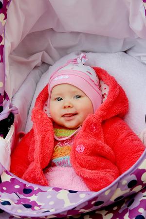 perambulator: little baby in red suit is smiling in the perambulator