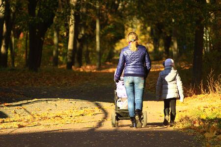 perambulator: woman with baby in perambulator and elder child walking in the autumn park
