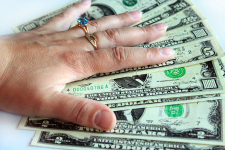 meanness: hand with rings holding US dollars isolated on a white background