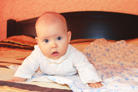 marvellous: little lovely baby lying on the bed in marvellous pose