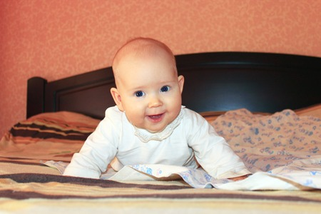 marvellous: little lovely baby lying and smiling on the bed in marvellous pose Stock Photo