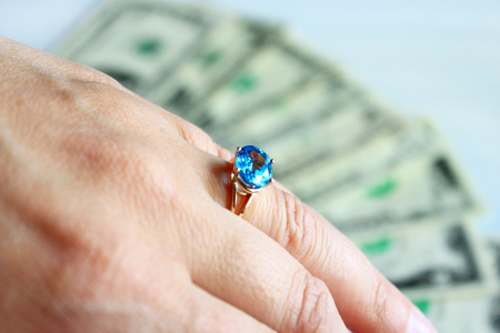 cupidity: Hand with topaz on the ring and dollars on the rare background
