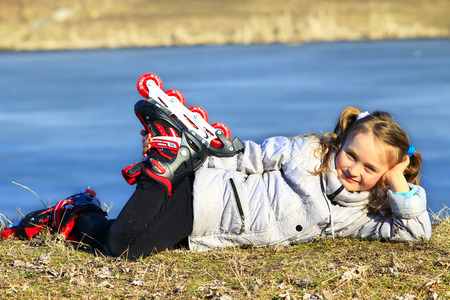 rollerskates: young girl in roller skates lays on the ground and smiles
