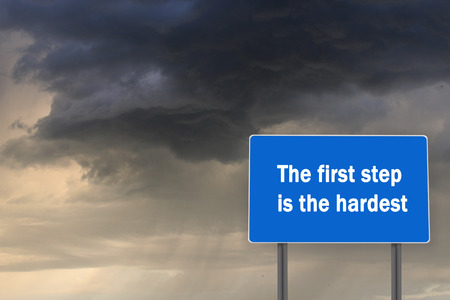 Billboard with inscription about first heardest step on the background of dark stormy sky
