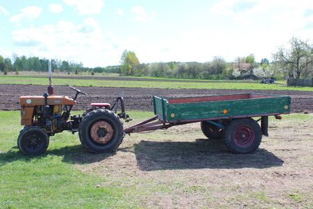 agronomic: old tractor with trailer in the village