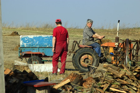 agronomic: rural men work with tractor with trailer in the village
