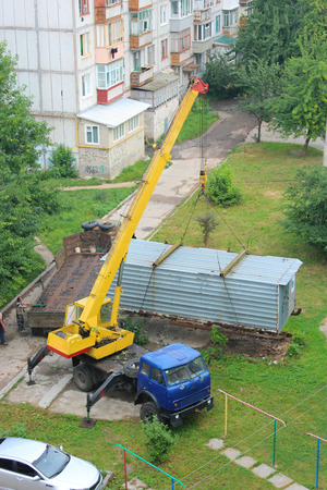 dormitory: truck with hoisting crane loading the wagon in the yard of dormitory area Archivio Fotografico