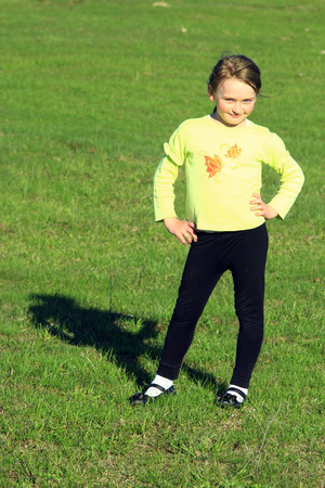 gratifying: little girl standing at in the business position on the green grass