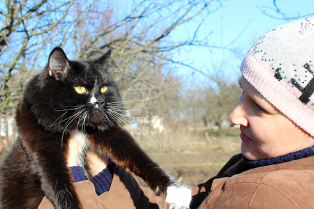 affectionate: woman looking at black cat with white tie in the spring