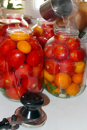 red tasty tomatos in jars prepared for preservation