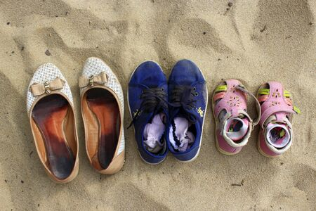 footgear: footwear left by mother and her daughters whith went to swim in the river Stock Photo