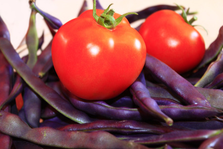 haricot: two red tomatoes and lilac pods of haricot Stock Photo