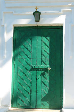 smithery: closed green church doors and small lantern above it