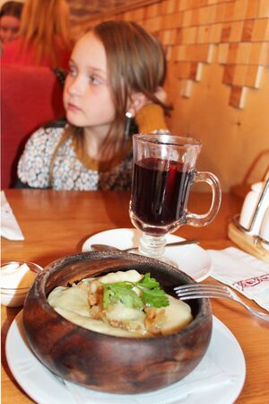 widespread: young girl in the restaurant. varenyky with fried slices of bacon. Slavic dish is most widespread in the Ukrainian cuisine