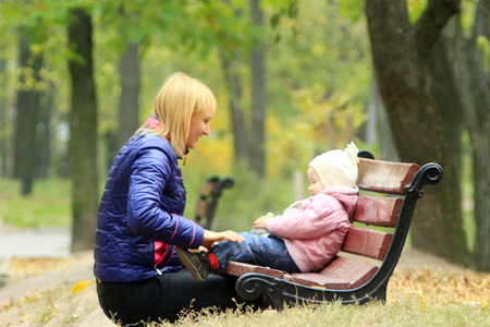 mother on bench: Mother plays with her daughter sitting on the bench in the park