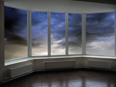 urban decline: office windows with dark thunder clouds beyond it Stock Photo