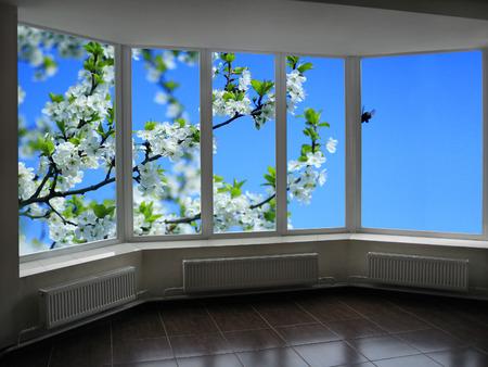 cereza: metal-plastic windows overlooking the garden with blossoming plum-tree Foto de archivo