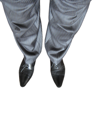 footgear: man feet in fashionable trousers isolated on the white