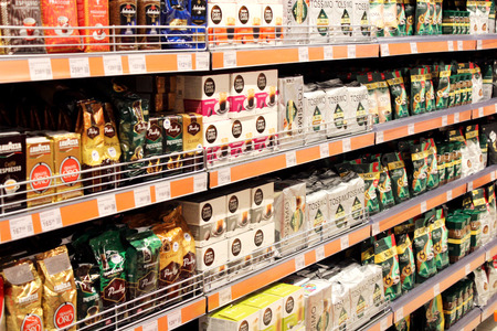 shop with a lot of different coffee packets on the shelves in supermarket