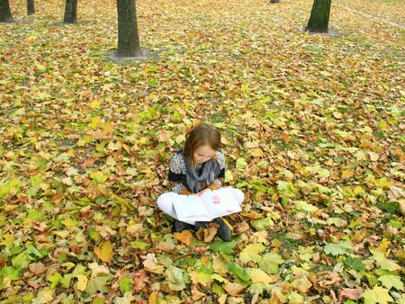 nine years old: young girl reads a book in the autumn park sitting on the ground
