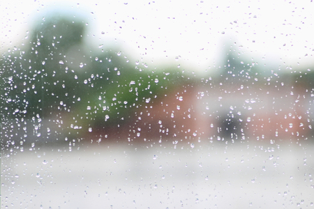 trickle down: its raining behind the window in the city