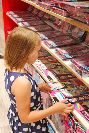nine years old: little girl chooses a book in a bookstore Editorial
