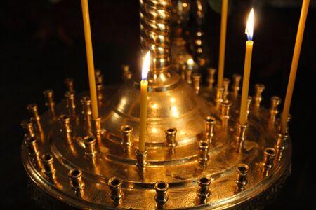 dimly: dimly burning church candles on candlesticks in church Stock Photo
