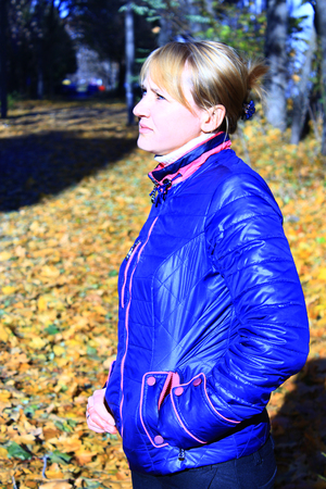outer clothing: modern fashionable woman in blue jacket looks up Stock Photo