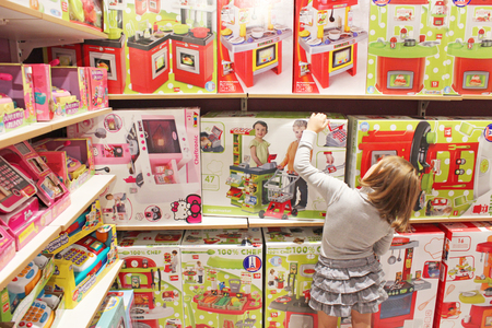 toy shop: little girl chooses a toy in a toy shop