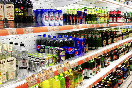 nonalcoholic beer: different kinds of beer and soft drinks like pepsi-cola with wide assortment on the shelves of supermarket Editorial