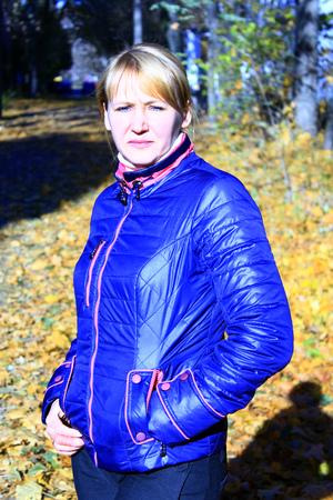 outer clothing: modern fashionable woman in blue jacket in Autumn park