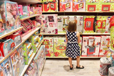 meisje kiest een pop in een speelgoedwinkel Redactioneel