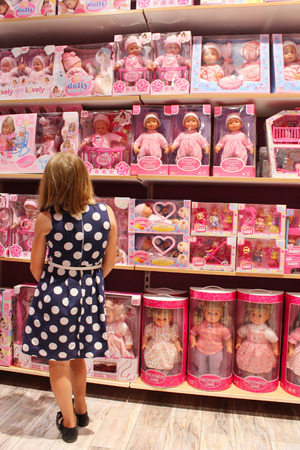 toy shop: little girl chooses a doll in a toy shop