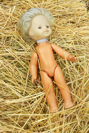 deplorable: old abandoned doll lays on the hay Stock Photo