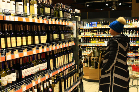 wine trade: woman chooses alcoholic drinks on the shelves of supermarket Editorial