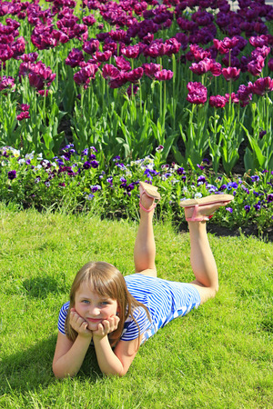 tulips in green grass: little fashionable girl lies on the green grass near the lilac tulips