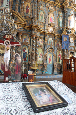 iconostasis: icon lies on the table by beautiful iconostasis with ancient icons set in wooden frame. Religious work of art in the church Editorial