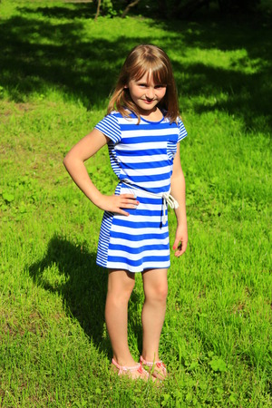 sympathetic: sympathetic little fashionable girl lies on the green grass
