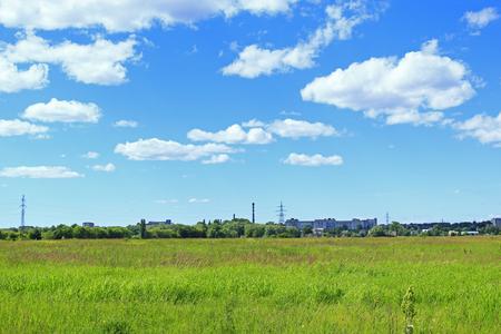 lejos: paisaje de verano con el campo de cielo azul y la hierba vista de la ciudad chimenea de la fábrica a lo lejos. la hierba verde en la vista de pradera y urbana mucho