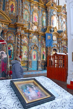 icon on the table in front of beautiful iconostasis with ancient icons set in wooden frame. Religious work of art in the church Stock Photo