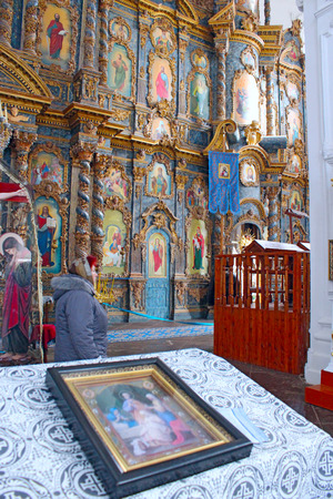 iconostasis: icon on the table in front of beautiful iconostasis with ancient icons set in wooden frame. Religious work of art in the church Editorial