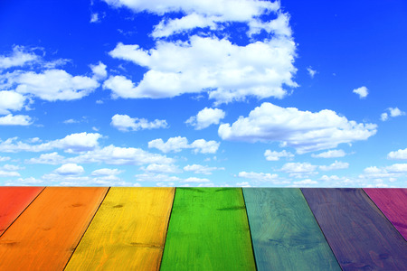 multicolored bright stand from wooden boards and blue sky with white clouds Stock Photo