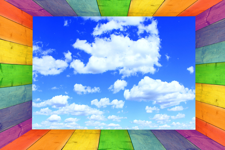 baguet: multicilored frame on the blue sky background with great white clouds Stock Photo