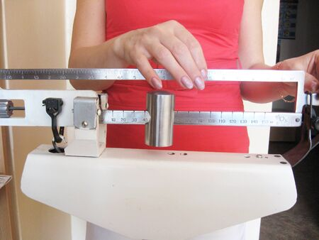 overeat: woman is weighed on the old mechanical scales Stock Photo