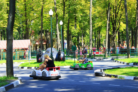 children with their parents drive the electric cars in Gorky park in Kharkiv