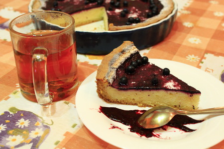 piece of fresh pie with bilberry on the plate and cup of tea Stock Photo