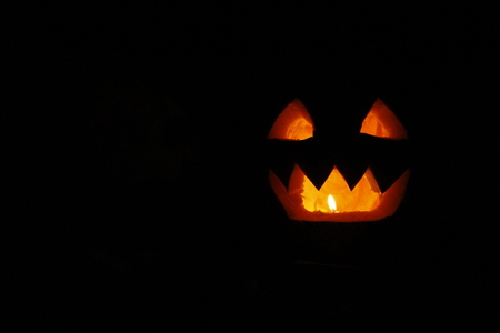 bared teeth: bared teeth of Halloween pumpkin ghost with burning candle within Stock Photo