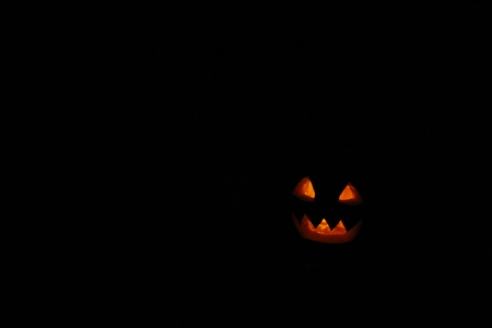 bared teeth: bared teeth of Halloween pumpkin ghost with burning candle within. Ghost of Halloween with black empty place for text
